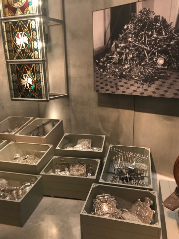 Display of valuables stolen from Jewish homes and synagogues Silverware but also stain glass windows were stolen. This display of them sorted in boxes but jumbled together was very striking and really hit home what had been lost in both spiritual and financial terms.