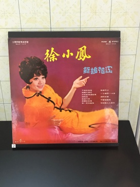 Ever versatile, the cheongsam in vibrant orange with beehive hairdo. Paula Tsui on the cover of her album 'New version of Peach Blossom River', 1970s