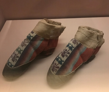 Booties with gradated red twill and kesi decoration, Han to Jin dynasty, unearthed from Niya tomb site in Minfeng county, Xinjiang, Xinjiang Archaeological Research Institute.